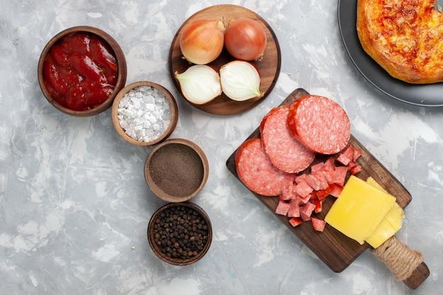 Bovenaanzicht verschillende kruiden met worst en tomatensaus op wit bureau