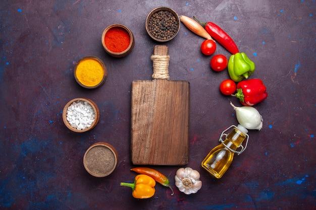 Bovenaanzicht verschillende kruiderijen met olie en groenten op het donkere oppervlak maaltijd voedsel plantaardige pittig