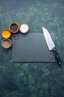 Bovenaanzicht verschillende kruiderijen op donkerblauw oppervlak voedsel kruiden zout peper kleur