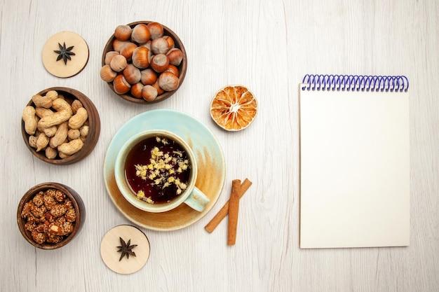 Bovenaanzicht verschillende noten in kleine potjes met kopje thee op witte bureaunoot snack walnoot hazelnoot