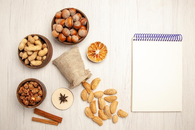 Bovenaanzicht verschillende noten in kleine potjes op witte bureaunoot snack walnoot hazelnoot
