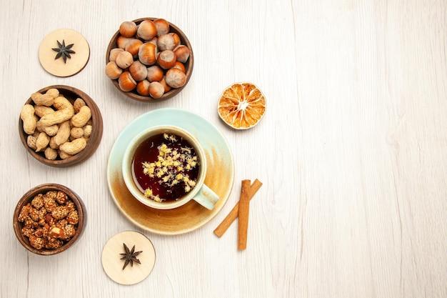Bovenaanzicht verschillende noten in kleine potten met kopje thee op witte bureau noten snack walnoot hazelnoot