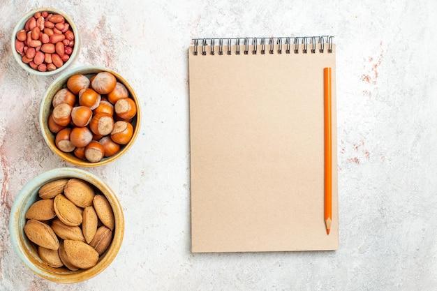 Bovenaanzicht verschillende noten in kleine potten op de witte achtergrond noot snack verse walnoot hazelnoot pinda