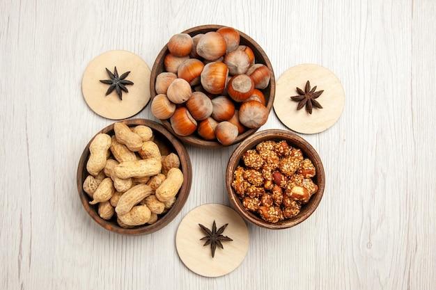 Bovenaanzicht verschillende noten in kleine potten op wit bureau snack walnoot hazelnoot noot
