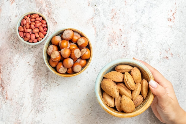 Bovenaanzicht verschillende noten in kleine potten op witte achtergrond noten snack verse walnoot hazelnoot pinda