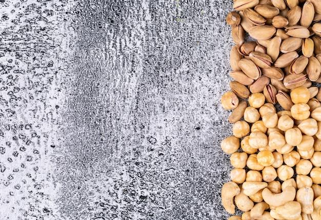 Bovenaanzicht verschillende noten met amandelen en hazelnoten op donkere stenen tafel