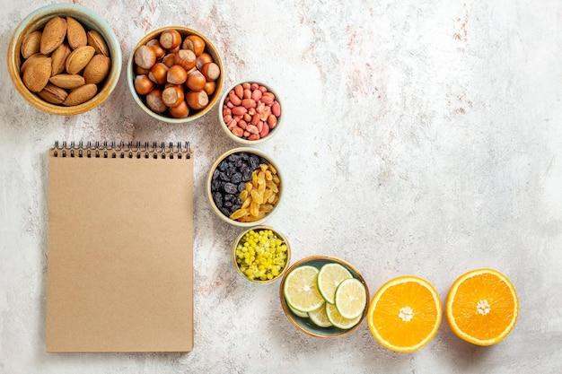 Bovenaanzicht verschillende noten met citrusvruchten op een witte achtergrond noot snack verse walnoot hazelnoot pinda