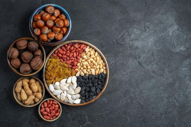 Bovenaanzicht verschillende noten met rozijnen en gedroogd fruit op de grijze achtergrond noten snack rozijnen droog fruit noten