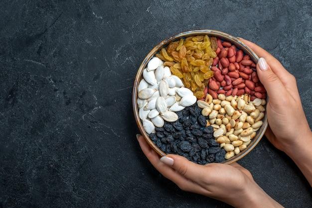 Bovenaanzicht verschillende noten met rozijnen en gedroogd fruit op de grijze noten snack hazelnoot walnoot pinda