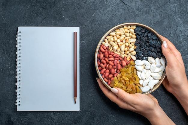 Bovenaanzicht verschillende noten met rozijnen en gedroogd fruit op grijze achtergrond noten snack hazelnoot walnoot pinda's