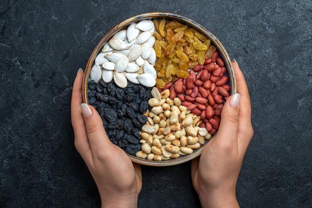 Bovenaanzicht verschillende noten met rozijnen en gedroogd fruit op het grijze oppervlak noten snack hazelnoot walnoot pinda