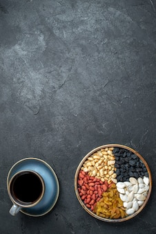 Bovenaanzicht verschillende noten met rozijnen en kopje koffie op de donkergrijze achtergrond noten snack walnoot pinda