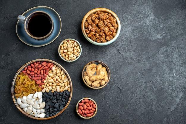 Bovenaanzicht verschillende noten met rozijnen en kopje koffie op donkergrijze noten snack walnoot pinda