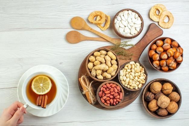 Bovenaanzicht verschillende noten pinda's hazelnoten en walnoten met kopje thee op witte tafel