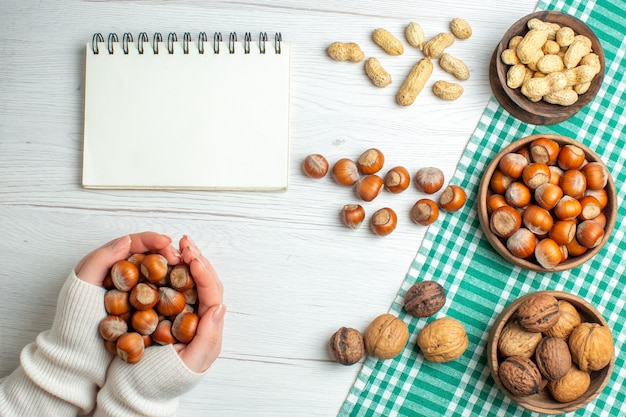 Bovenaanzicht verschillende noten, pinda's, hazelnoten en walnoten op witte tafel in vrouwelijke handen