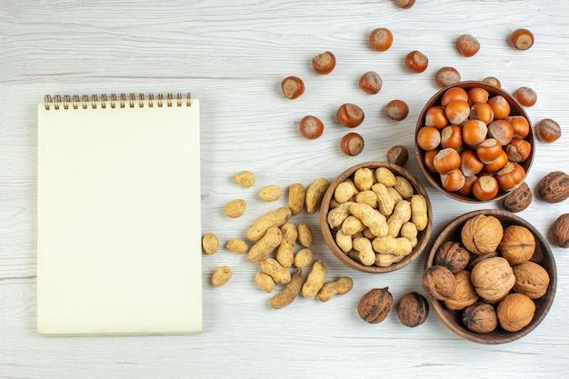 Bovenaanzicht verschillende noten, pinda's, hazelnoten en walnoten op witte tafel