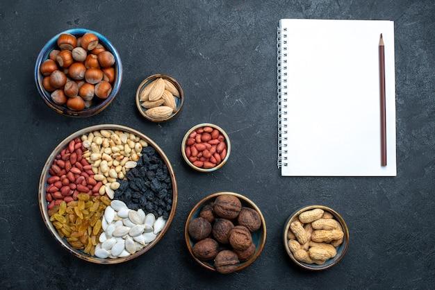 Bovenaanzicht verschillende noten samenstelling van snacks met blocnote op donkergrijze achtergrond noot snack foto walnoot hazelnoot