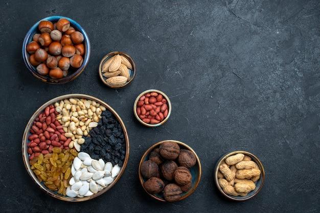 Bovenaanzicht verschillende noten samenstelling van snacks op donkergrijze achtergrond noten snack foto walnoot hazelnoot