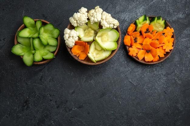 Bovenaanzicht verschillende ontworpen groenten in potten op donkergrijze ruimte