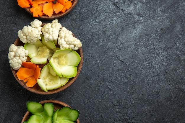 Bovenaanzicht verschillende ontworpen groenten in potten op een grijze ruimte