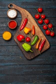 Bovenaanzicht verschillende paprika's met kruiden op donker bureau