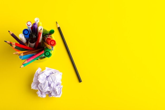 Bovenaanzicht verschillende potloden met viltstiften op geel oppervlak