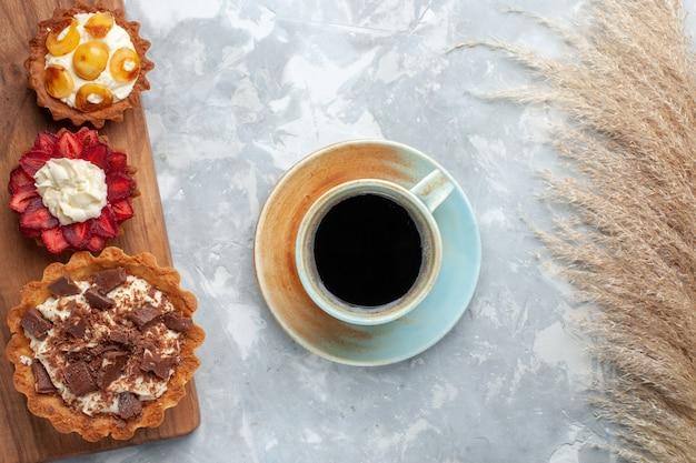 Bovenaanzicht verschillende romige taarten met chocolade en fruit, samen met thee op het witte bureau, cake bak koekje zoete suiker fruit