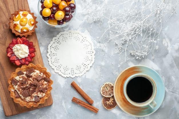 Bovenaanzicht verschillende romige taarten met kersen en thee op de lichttafel cake bakken koekje zoete suiker fruit