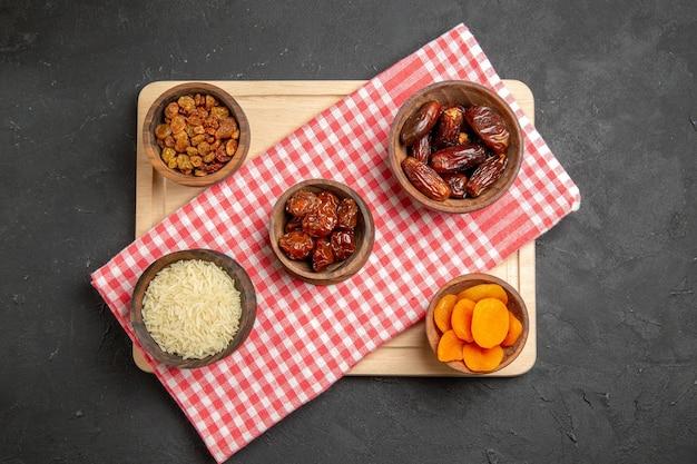 Bovenaanzicht verschillende rozijnen khurma en ander droog fruit op grijs oppervlak droog fruit maaltijd zuur