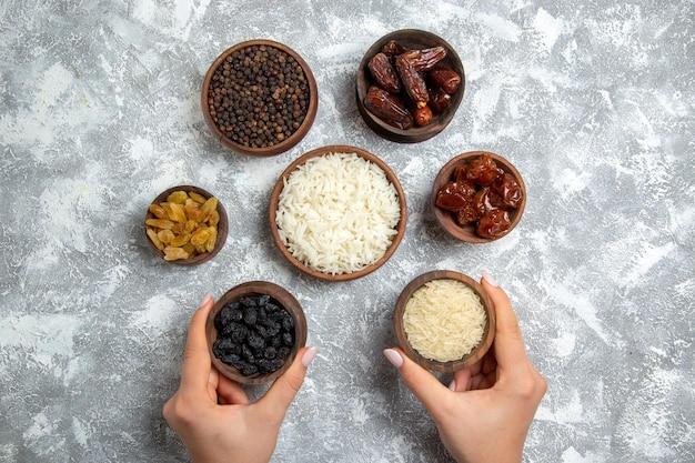 Bovenaanzicht verschillende rozijnen met khurma en rijst op witruimte