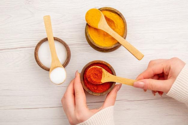 Bovenaanzicht verschillende smaakmakers in kleine potten op wit bureau