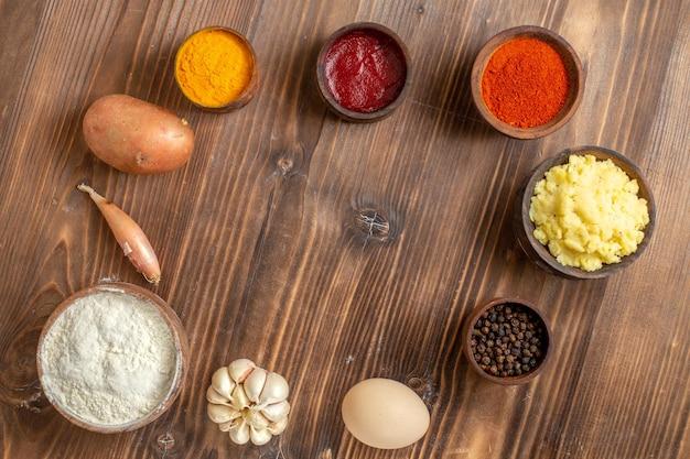 Bovenaanzicht verschillende smaakmakers met aardappelpuree en knoflook op het bruine houten bureau, pittige peper, rijp aardappelvoedsel
