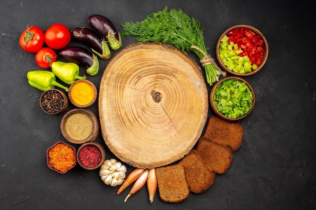 Bovenaanzicht verschillende smaakmakers met groene groenten en donkere broodbroden op de donkere achtergrond saladekruiden brood gezondheidsvoedsel