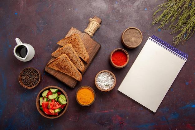 Bovenaanzicht verschillende smaakmakers met groenten brood broden op donkere ondergrond