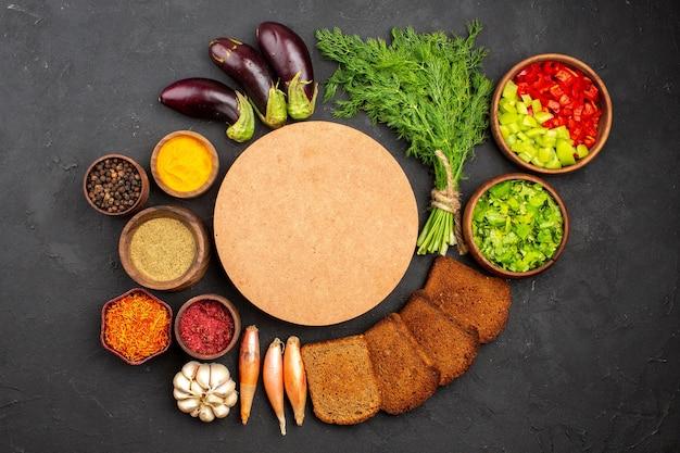 Bovenaanzicht verschillende smaakmakers met groenten en donkere broodbroden op donkere achtergrond saladekruiden broodgezondheidsvoedsel