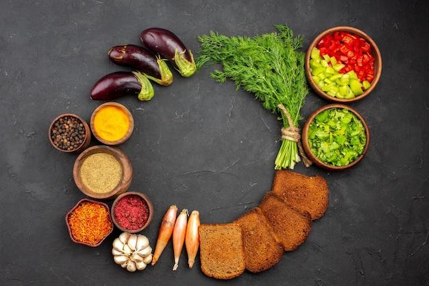 Bovenaanzicht verschillende smaakmakers met groenten en donkere broodbroden op donkere achtergrond saladekruiden broodmaaltijd gezondheid