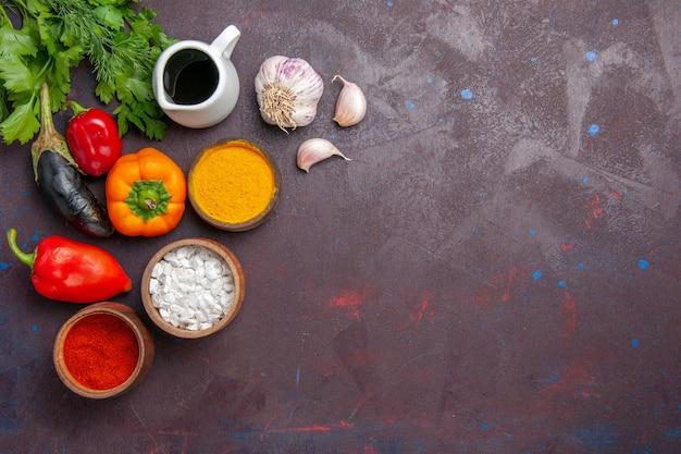 Bovenaanzicht verschillende smaakmakers met groenten op donkere achtergrond salade maaltijd voedingsproduct