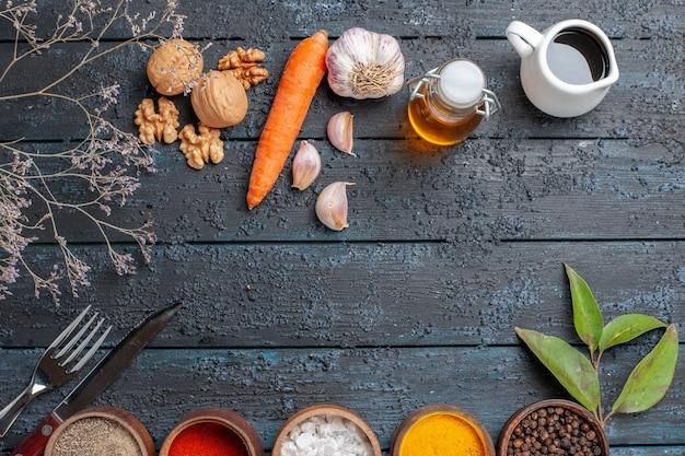 Bovenaanzicht verschillende smaakmakers met knoflook en walnoten op donkerblauwe bureau pittige rijpe kleur