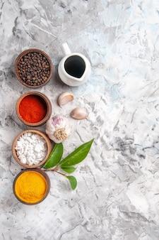 Bovenaanzicht verschillende smaakmakers met knoflook op witte tafelpeperkruiden