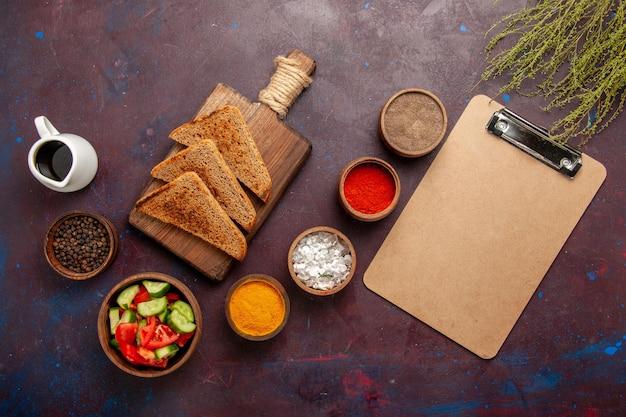 Bovenaanzicht verschillende smaakmakers met salade brood broden en notitieblok op donkere ondergrond