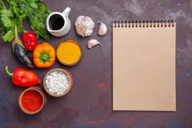 Bovenaanzicht verschillende smaakmakers met verse groenten op de donkere achtergrond salade groente product voedsel maaltijd