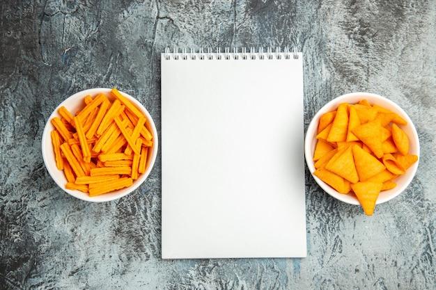 Bovenaanzicht verschillende snacks beschuit en kaas cips op lichte ondergrond