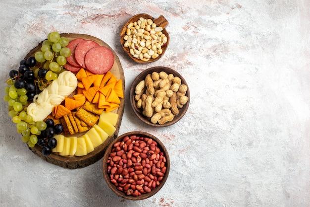 Bovenaanzicht verschillende snacks cips worst kaas en verse druiven met noten op witte ruimte