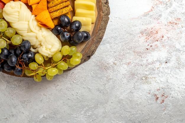 Bovenaanzicht verschillende snacks cips worst kaas en verse druiven op de lichte witte ruimte
