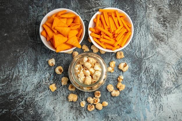 Bovenaanzicht verschillende snacks popcorn beschuit en cips op het donkere oppervlak