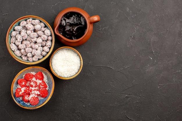 Bovenaanzicht verschillende snoepjes met chocoladesiroop op donkere oppervlaktekleur snoeptheekoekje