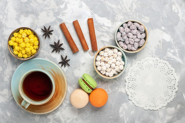 Bovenaanzicht verschillende snoepjes met franse macarons en kopje thee op witte achtergrond kandijsuiker zoete bak cake thee taart cookie