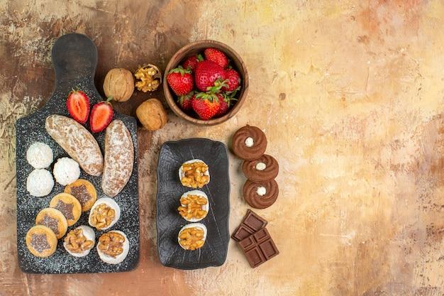 Bovenaanzicht verschillende snoepjes met koekjes en fruit op het lichtbureau