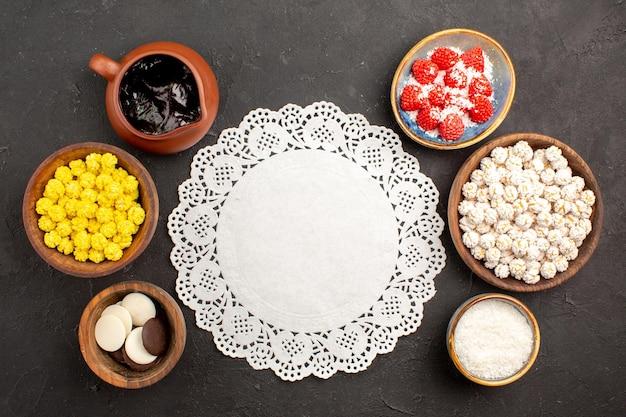 Bovenaanzicht verschillende snoepjes met koekjes op donkere oppervlaktekleur snoep theekoekje