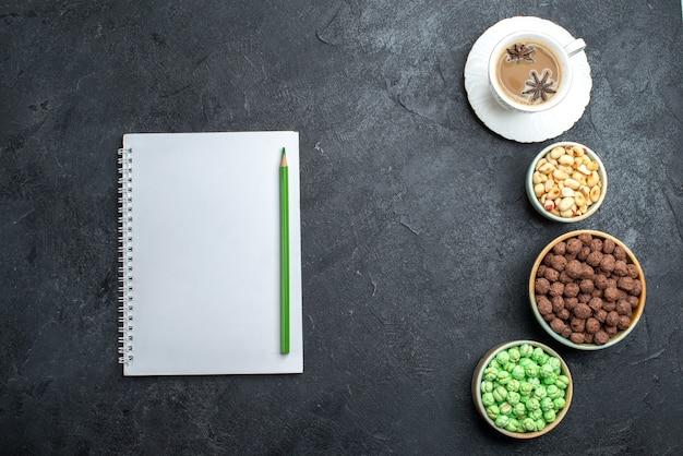 Bovenaanzicht verschillende snoepjes met kopje koffie en blocnote op donkergrijze achtergrond kandijsuiker zoete cake bonbon goodie